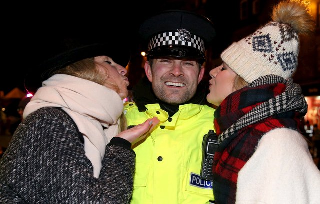 Girls kiss a police officer during the Hogmanay celebrations in Edinburgh, Scotland, December 31, 2015. (Photo by Russell Cheyne/Reuters)