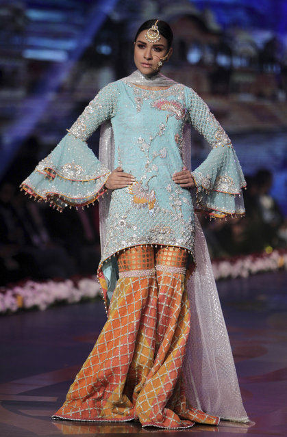 A model presents a creation by designer Wardha Saleem during Bridal Couture Week 2016 in Lahore, Pakistan, Sunday, November 27, 2016. (Photo by K.M. Chaudary/AP Photo)