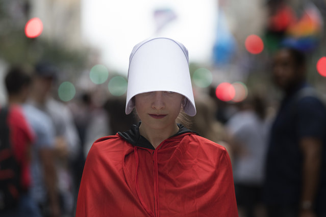 "A unidentified woman protests at Broad Street for the pending arrival of Vice President Mike Pence at the Union League, in Philadelphia, Monday, July 23, 2018. Dozens of demonstrators dressed as characters from the novel-turned-TV series ""The Handmaid's Tale"" descended on downtown Philadelphia to protest Pence's visit. (Photo by Jose F. Moreno/The Philadelphia Inquirer via AP Photo)"