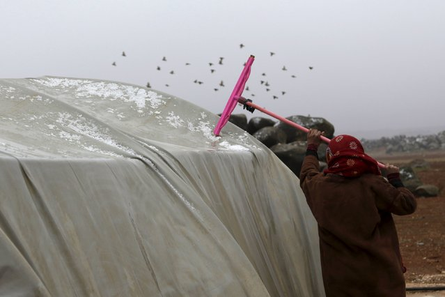 A girl removes snow and water from the top of a tent in Jerjnaz camp, for internally displaced people, during cold weather in Idlib province, Syria, January 5, 2016. (Photo by Khalil Ashawi/Reuters)