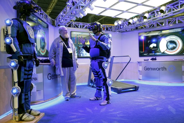 Bran Ferren (C), founder of Applied Minds, listens to a journalist dressed in an R70i aging suit during a preview of the Genworth booth at the 2016 CES trade show in Las Vegas, Nevada, January 5, 2016. The suits simulate various aging conditions and will be used in a national tour to educate and build empathy for the aging process, said spokeswoman Alexandra Osorio. (Photo by Steve Marcus/Reuters)