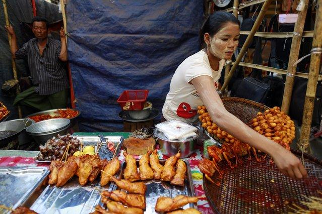 A woman sells fried chicken at the Kyaik-Khauk pagoda festival in the Tanlyin township outside Yangon February 4, 2015. (Photo by Soe Zeya Tun/Reuters)