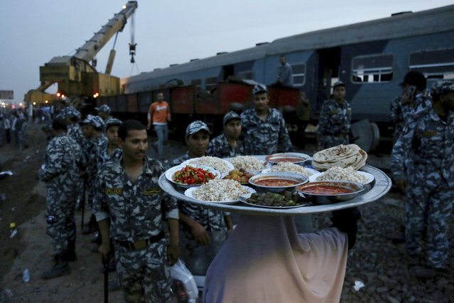 A woman brings food for security forces to break their fast during the holy month of Ramadan, at the site of a passenger train that derailed injuring around 100 people, near Banha, Qalyubia province, Egypt, Sunday, April 18, 2021. At least eight train wagons ran off the railway, the provincial governor's office said in a statement. (Photo by Fadel Dawood/AP Photo)