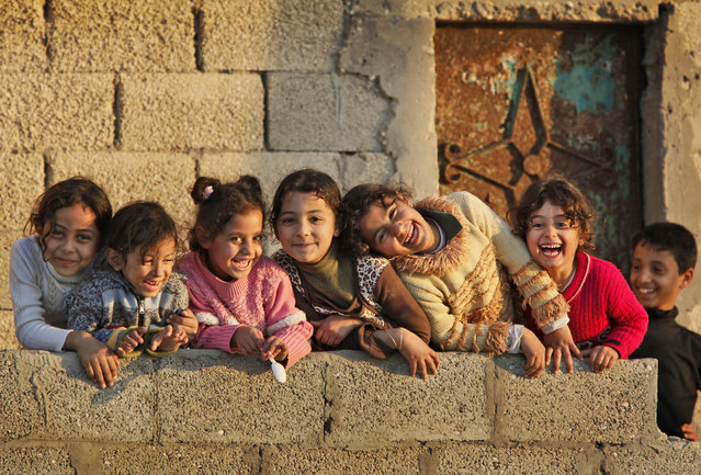 Young Palestinian girls giggle as they are photographed in front of a house at sunset near where a shell fired from an Israeli gunboat landed earlier Thursday, January 22, 2009, according to local residents, in the Shati refugee camp in Gaza City, in the Gaza strip. (Photo by Ben Curtis/AP Photo)