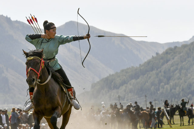 In this photo taken on Thursday, September 6, 2018, a women releases an arrow during an archery competition during the Third Nomad Games, in Cholpon-Ata, 250 kilometers (156 miles) of Bishkek, Kyrgyzstan. The Central Asian nation of Kyrgyzstan held its biennial Nomad Games to promote and celebrate traditional sports of nomadic people. The week-long competition, which is held in a gorge near the picturesque Lake Issyk-Kul, feature traditional sports of nomad peoples such as horseback wrestling and goat polo. (Photo by Vladimir Voronin/AP Photo)
