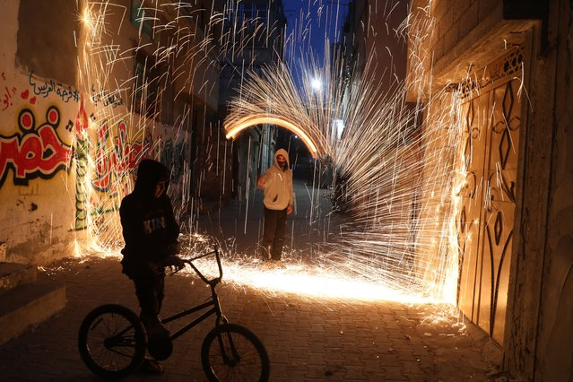 A Palestinian youth swings a homemade fireworks sparkler, as people celebrate on the night ahead of the Muslim holy fasting month of Ramadan, in Gaza City on April 11, 2021. (Photo by Majdi Fathi/NurPhoto/Rex Features/Shutterstock)