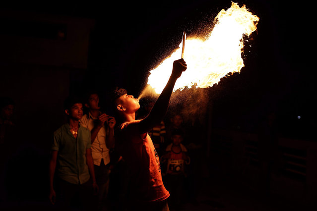 A Bangladeshi youth blows fire from his mouth during the Poush Sankranti festival in the old part of Dhaka, Bangladesh, 14 January 2016. Poush Sankranti is mainly a harvest festival known as Sakrain in Old Dhaka. People celebrate it with different activities like flying kites on rooftops, listening loud music and fire spinning. (Photo by Abir Abdullah/EPA)