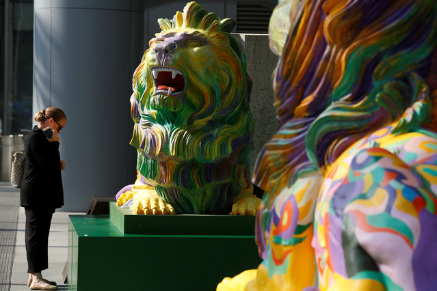 """A passerby reads an introduction on """"Stephen"""", one of the two lions in rainbow colors to show support for the LGBT (lesbian, gay, bisexual and transgender) community, being newly displayed at HSBC's main branch in Hong Kong, China December 7, 2016. (Photo by Bobby Yip/Reuters)"""