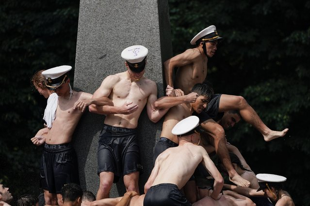 Midshipmen freshmen, known as Plebes, pile on while trying to reach the top of the Herndon Monument during the Herndon Monument Climb at the U.S. Naval Academy, Saturday, May 22, 2021, in Annapolis, Md. Freshmen, known as Plebes, participate in the climb to celebrate finishing their first year at the academy. The climb, which took 3:41 hours to complete, was reached when Midshipman 4th Class Michael Lancaster, 19, center, of Signal Hill, Tenn., of the 14th Company, placed a cover atop the monument. (Photo by Julio Cortez/AP Photo)