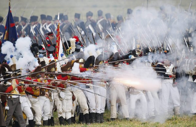 Performers wearing 19th century French military uniforms fire their weapons as they attack Allied forces during a reenactment of the Battle of the Nations, in a field in the village of Markkleeberg near Leipzig October 20, 2013. (Photo by Fabrizio Bensch/Reuters)