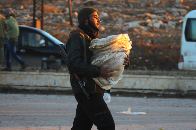 A rebel fighter carries bread for evacuees from rebel-held east Aleppo, upon their arrival to the town of al-Rashideen, which is held by insurgents, Syria December 15, 2016. (Photo by Ammar Abdullah/Reuters)