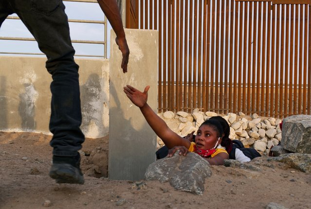 A Haitian migrant family member reaches out for help while emerging from a rocky canal adjacent to a gap in the U.S. border wall in Yuma, Ariz., Wednesday, June 9, 2021. (Photo by Eugene Garcia/AP Photo)