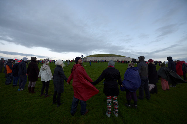 Revellers wait for the sun to appear during winter solstice at the 5000 year old stone age tomb of Newgrange in the Boyne Valley at sunrise in Newgrange, Ireland, December 21, 2016. (Photo by Clodagh Kilcoyne/Reuters)