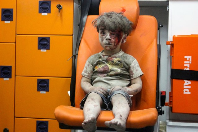 Omran, a 4-year-old Syrian boy covered in dust and blood, sits in an ambulance after being rescued from the rubble of a building hit by an airstrike in the rebel-held Qaterji neighborhood of the northern Syrian city of Aleppo, August 17, 2016. (Photo by 