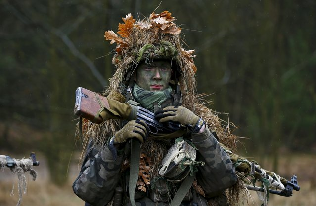 Damian Trynkiewicz carries his weapon during territorial defence training organised by SJS Strzelec (Shooters Association), paramilitary group in the forest near Minsk Mazowiecki, eastern Poland March 14, 2014. (Photo by Kacper Pempel/Reuters)