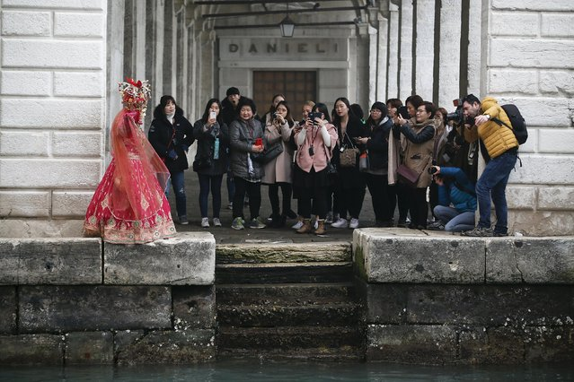 A masked reveller (L) is pictured by tourists during the Venice Carnival, in San Marco Piazza January 30, 2016. (Photo by Alessandro Bianchi/Reuters)