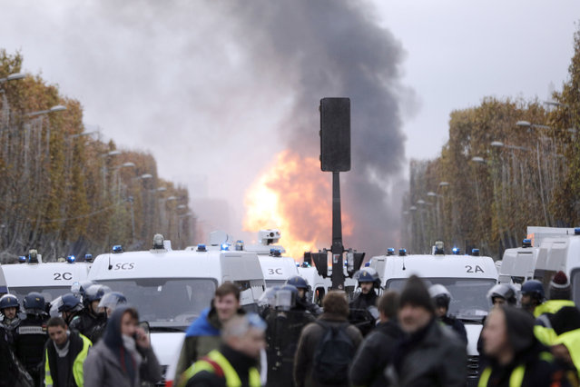 A huge explosion is seen on the famed Champs-Elysees avenue, after protesters, called the yellow jackets, set on fire a construction trailer during clashes with riot police as they protest against the fuel taxes, in Paris, France, Saturday, Novemner 24, 2018. French police fired tear gas and water cannons to disperse demonstrators in Paris Saturday, as thousands gathered in the capital and staged road blockades across the nation to vent anger against rising fuel taxes and Emmanuel Macron's presidency. (Photo by Kamil Zihnioglu/AP Photo)