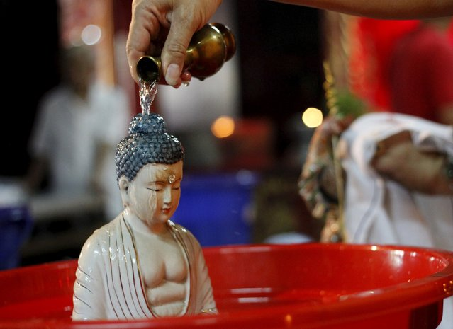 A volunteer cleans a statue ahead of the Lunar New Year celebrations at Vihara Dharma Bhakti Temple in Jakarta, Indonesia, February 3, 2016. (Photo by Garry Lotulung/Reuters)