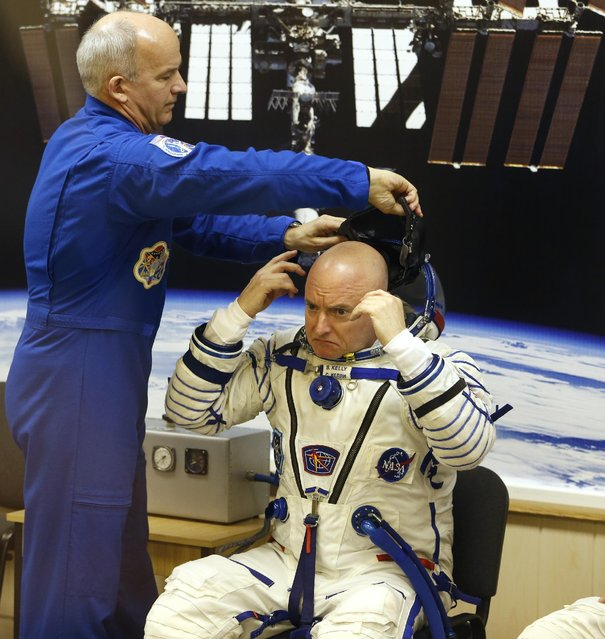 Back crew member U.S. astronaut Jeff Williams, left, helps U.S. astronaut Scott Kelly, a crew member of the mission to the International Space Station, ISS, to put on his helmet during inspection of his space suit, prior to the launch of the Soyuz-FG  rocket  at the Russian-leased Baikonur cosmodrome, Kazakhstan, Friday, March 27, 2015. (Photo by Dmitry Lovetsky/AP Photo)