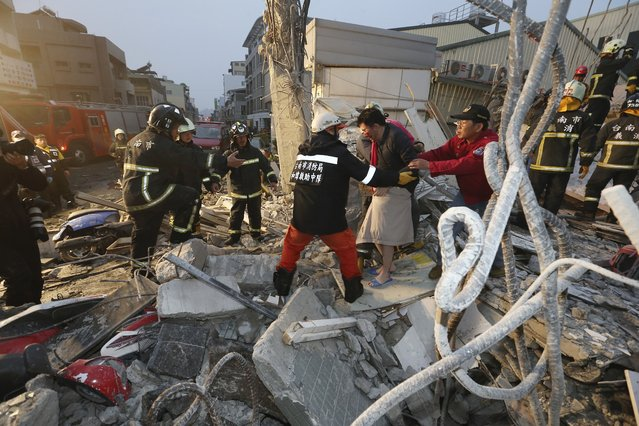 Rescue workers guide a man from the rubble of a toppled building after an earthquake in Tainan, Taiwan, Saturday, February 6, 2016. (Photo by AP Photo)