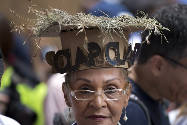 """A woman wears a cardboard hat with dry grass on top and letters in Spanish that read """"CLAP"""", referring to government subsidized food through the """"CLAP"""" program, which stands for Local Committees of Supply and Production, during a protests against the government of President Nicolas Maduro in Caracas, Venezuela, Thursday, August 16, 2018. (Photo by Ariana Cubillos/AP Photo)"""