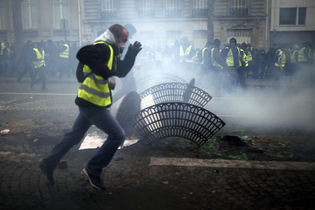 Demonstrators run away during clashes Saturday, December 8, 2018 in Paris. (Photo by Rafael Yaghobzadeh/AP Photo)