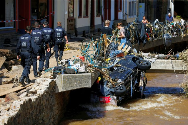 Police officers walk by a damaged car in an area affected by floods caused by heavy rainfalls in Bad Muenstereifel, Germany, July 18, 2021. (Photo by Thilo Schmuelgen/Reuters)
