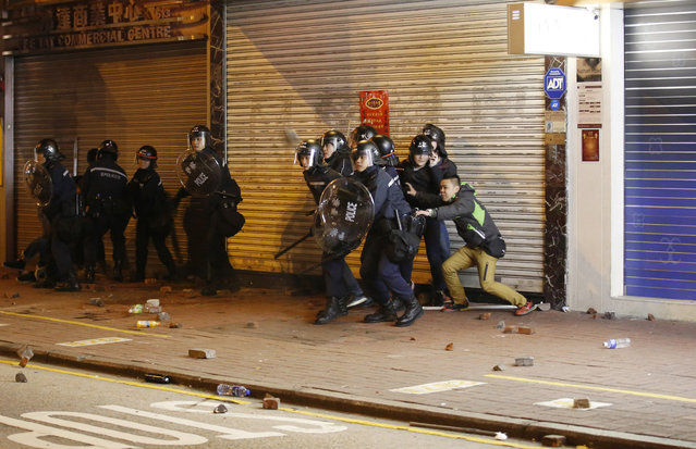 Riot police try to block the bricks thrown by the protesters on a street in Mongkok district of Hong Kong, Tuesday, February 9, 2016. (Photo by Kin Cheung/AP Photo)
