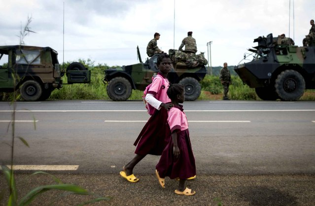 Children walk, next to French militaries, along a road in Cameroon on December 5, 2013. A UN Security Council resolution on Thursday gave French and African troops the green light to restore order in the Central African Republic, the latest in a string of military campaigns by France in its former colony. (Photo by Fred Dufour/AFP Photo)