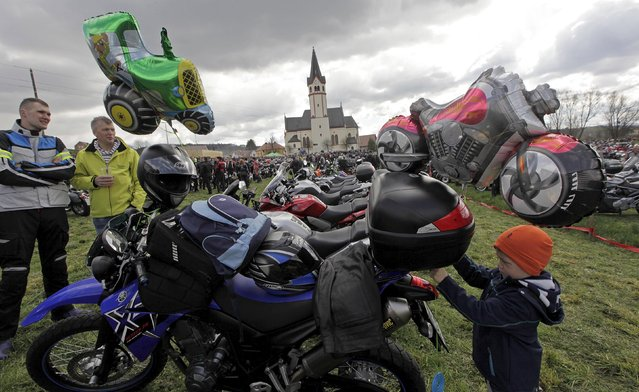 A boy ties a balloon to a motorcycle during the first gathering of motorists at the beginning of the spring season in Mirna Pec April 6, 2015. (Photo by Srdjan Zivulovic/Reuters)