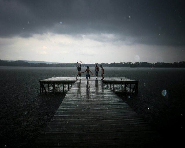 """""""Be Cheerful Even in the Darkest of Times"""". In your youth, nothing can stop you from enjoying time with your friends. Even a large rainstorm during a summer swim can't stop you from creating wonderful memories. You may grow up and forget the names, but you'll always remember the moments like these that make up your childhood. This photograph is a picture of my friends on a dock at City Park in Scottsboro Alabama. (Photo and caption by Samantha Fortenberry (USA)/2014 Sony World Photography Awards)"""
