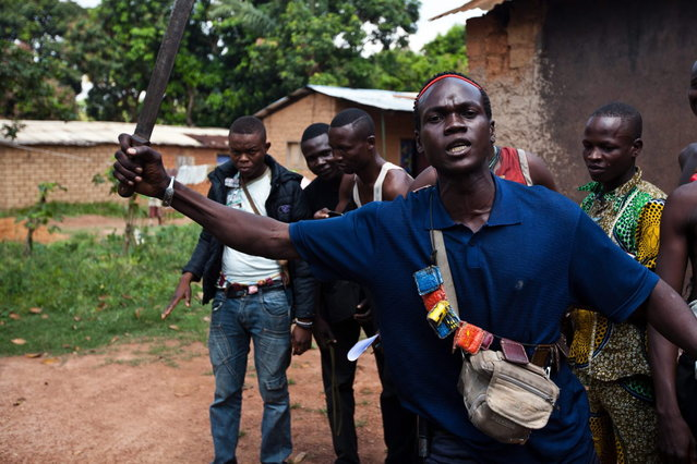 An Anti-Balaka fighter, member of a militia opposed to the Seleka rebel group, lifts up a machete threatening any Seleka that may attack, on the outskirts of the Boy-Rabe neighborhood in Bangui on December 14, 2013. (Photo by Ivan Lieman/AFP Photo)