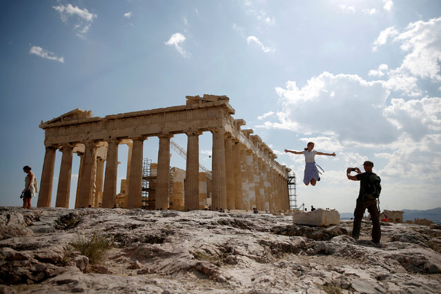 Tourists take a picture in front of the temple of the Parthenon atop the Acropolis in Athens, Greece July 20, 2018. (Photo by Costas Baltas/Reuters)