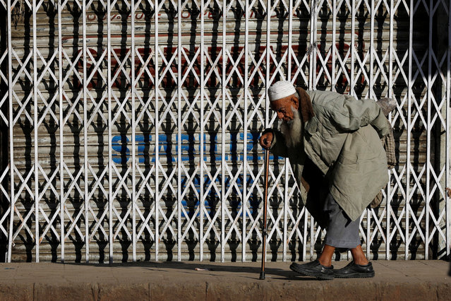 A man walks in the sunlight to warm himself on an early cold morning in Karachi, Pakistan on December 20, 2018. (Photo by Akhtar Soomro/Reuters)