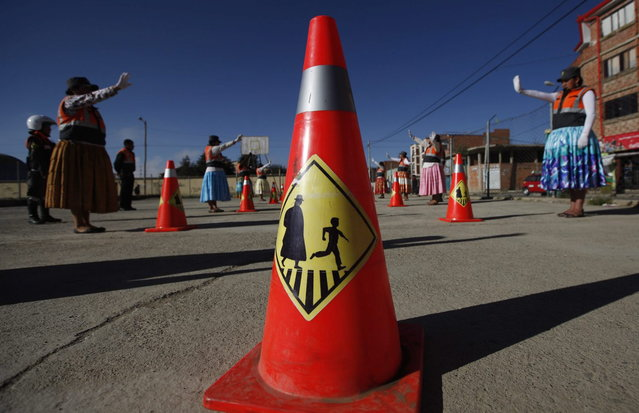 """This November 28, 2013 photo shows a traffic cone adorned with a silhouette of a """"cholita"""", a child and a crosswalk, at a practice session for Aymara women training to direct traffic in El Alto, Bolivia. (Photo by Juan Karita/AP Photo)"""