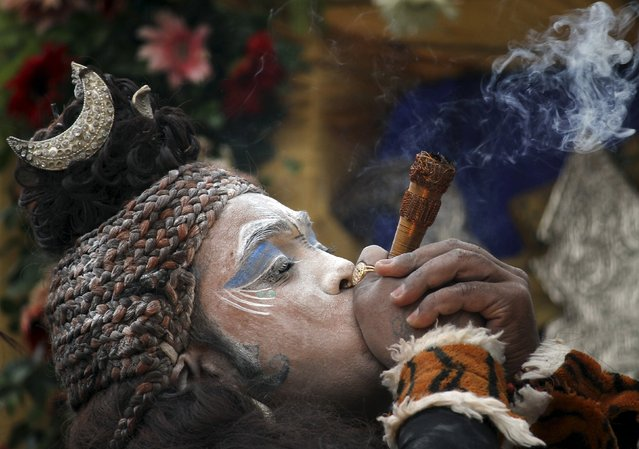 A man dressed as Hindu god Shiva, smokes during an annual Hindu religious festival locally known as Shyam Baba festival in Ajmer, in the desert Indian state of Rajasthan, April 12, 2015. (Photo by Himanshu Sharma/Reuters)