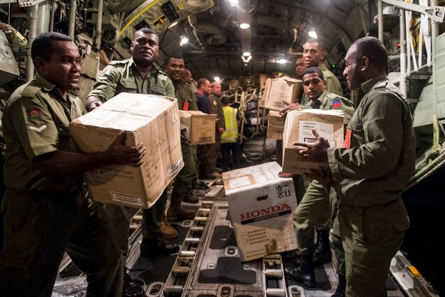 Aid supplies including generators, ration packs and water containers are unloaded by Fijian soldiers from a Royal New Zealand Air Force C-130 Hercules aircraft after Cyclone Winston in Suva, Fiji, in this handout image supplied by the New Zealand Defence Force February 23, 2016. (Photo by Reuters/NZ Defence Force)