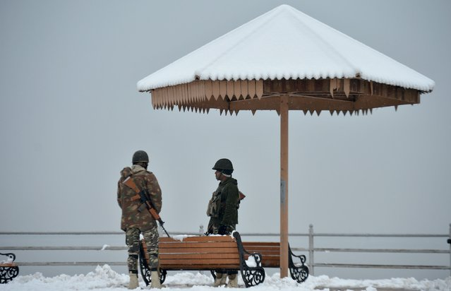 Indian paramilitary troopers stand guard on the shores of Dal Lake during fresh snowfall in Srinagar on January 16, 2017. (Photo by Tauseef Mustafa/AFP Photo)