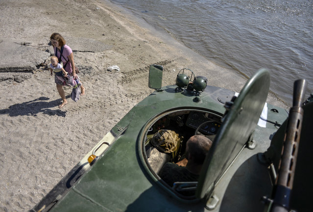A woman carries her baby past an APC of the Shakhtarsk battalion  on a beach in Mariupol on September 15, 2014. US-led military exercises began in Ukraine on Monday after a day of deadly fighting between government forces and pro-Russian rebels in the restive east that has piled pressure on a shaky 10-day-old truce. (Photo by Aleksey Chernyshev/AFP Photo)