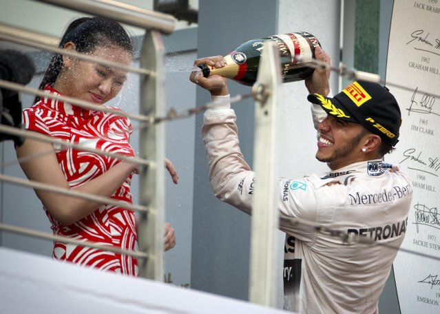 Mercedes driver Lewis Hamilton of Britain sprays champagne on a track attendant on the podium after winning the Chinese Formula One Grand Prix at Shanghai International Circuit in Shanghai, China, Sunday, April 12, 2015. (Photo by Mark Schiefelbein/AP Photo)