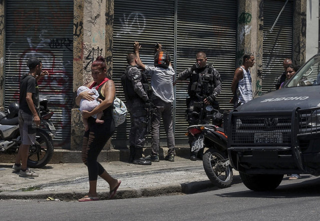 A woman carries a baby as she walks past police searching several men, during an operation targeting drug traffickers in the Santa Teresa neighborhood of Rio de Janeiro, Brazil, Friday, February 8, 2019. Law enforcement officials in Brazil's second largest city say that at least 11 suspected drug traffickers were killed in a shootout with police in a slum located in the bohemian Santa Teresa neighborhood. (Photo by Carson Gardiner/AP Photo)