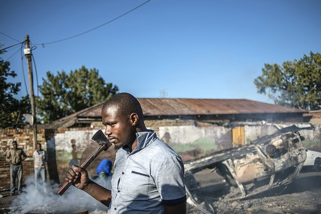 A man carries an axe as he walks past a burnt out vehicle near the Jeppies Hostles, where  foreign nationals are living, in the Jeppestown area of Johannesburg, on April 17, 2015 after residence from the Jeppie Hostles, purportedly torched the vehicle in the early hours. (Photo by Mujahid Safodien/AFP Photo)