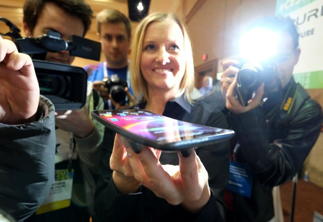 "Journalists watch presentation of LG G Flex phone during the first press event ""CES Unveiled"" at the Mandalay Bay Convention Center prior to the 2014 International CES in Las Vegas, Nevada on January 05, 2014. (Photo by Joe Klamar/AFP Photo)"