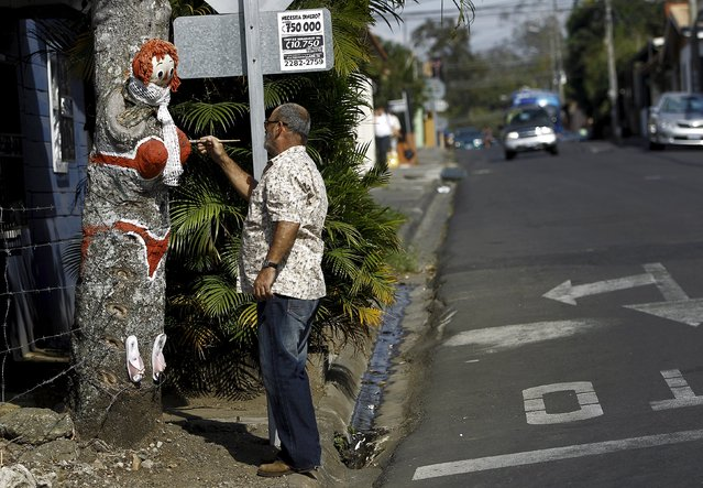 """Resident Gonzalo Sanchez paints """"The Woman in Red Bikini"""" on a mango tree, to replicate the figure of a woman wearing a bikini, at the corner of a street in the neighborhood of Escazu in San Jose, Costa Rica, March 1, 2016. (Photo by Juan Carlos Ulate/Reuters)"""