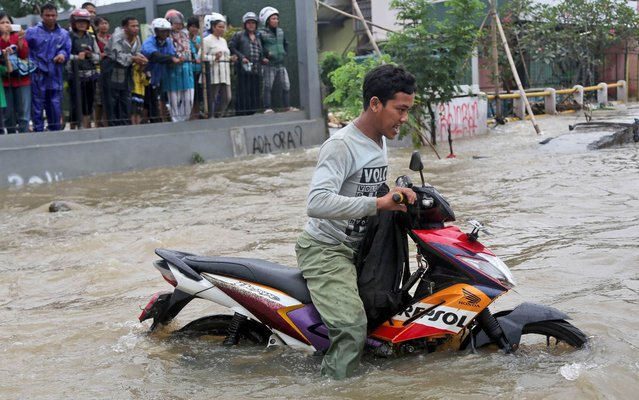 A man pushes his motorcycle to cross a flooded street in Jakarta, Indonesia, Monday. January 13, 2014. Heavy downpour has caused flooding that occur almost every year in parts of greater Jakarta due to bad city planning. (Photo by Tatan Syuflana/AP Photo)
