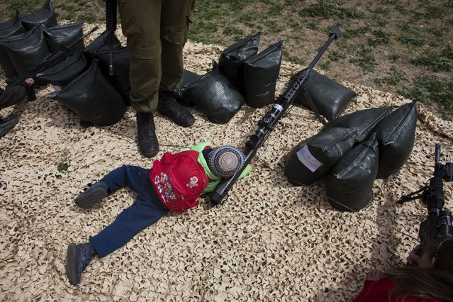 An Israeli boy looks through the sight of a weapon during a display of Israeli Defense Forces (IDF) equipment and abilities at the West Bank settlement of Kiryat Arba, April 23, 2015, during celebrations for Israel's Independence Day, marking the 67th anniversary of the creation of the state. (Photo by Ronen Zvulun/Reuters)