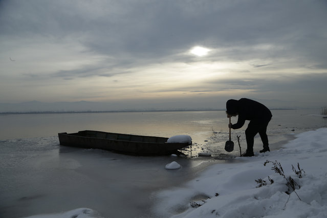 A man breaks the ice with the shovel to release his boat for fishing on Modrac lake in northern town of Lukavac, Bosnia, Sunday, January 27, 2019. Heavy snow descended on the Balkan countries causing havoc throughout the region. (Photo by Amel Emric/AP Photo)