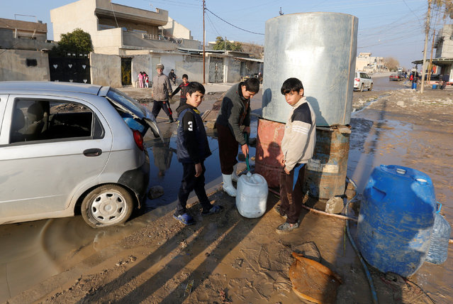 Children collect water for their families at al Zohour area in Mosul, Iraq, January 23, 2017. (Photo by Muhammad Hamed/Reuters)