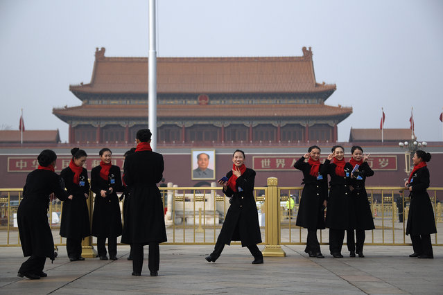 Hospitality staff enjoy the moment as they take pictures on Tiananmen Square during the opening session of the Chinese People's Political Consultative Conference (CPPCC) held at the Great Hall of the People in Beijing, Sunday, March 3, 2019. Thousands of delegates from around China have gathered in Beijing for the annual session of the country's rubber-stamp legislature and its advisory body. (Photo by Andy Wong/AP Photo)