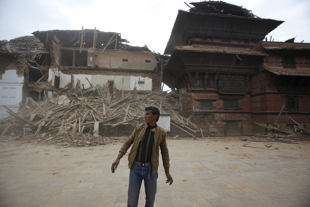 A man stands in front of a building that collapsed at Durbar Square, after an earthquake in Kathmandu, Nepal, Saturday, April 25, 2015. (Photo by Niranjan Shrestha/AP Photo)